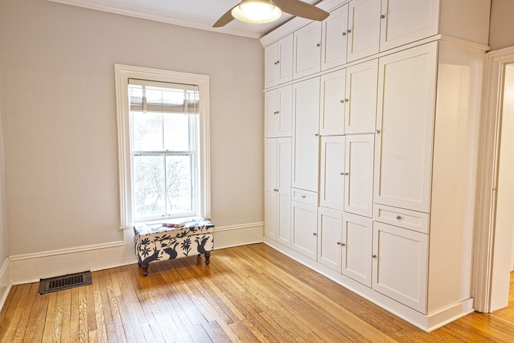 Room with big white cabinet and window seat