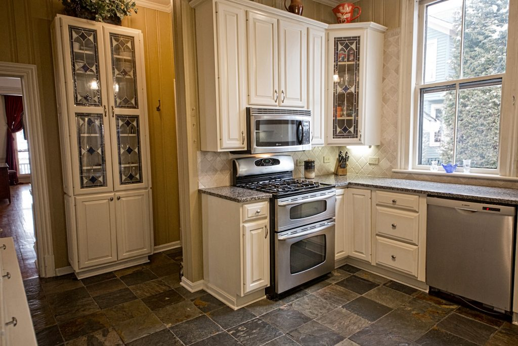 Kitchen with granite countertops, slate flooring and stainless steel appliances