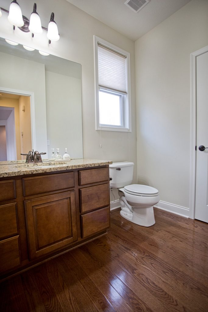 Bathroom with granite bathroom countertop and wooden cabinet