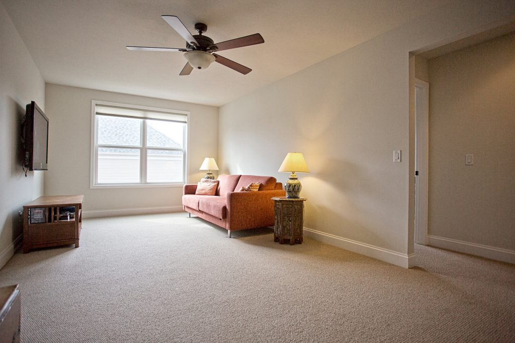 Room with flat screen tv and ceiling fan