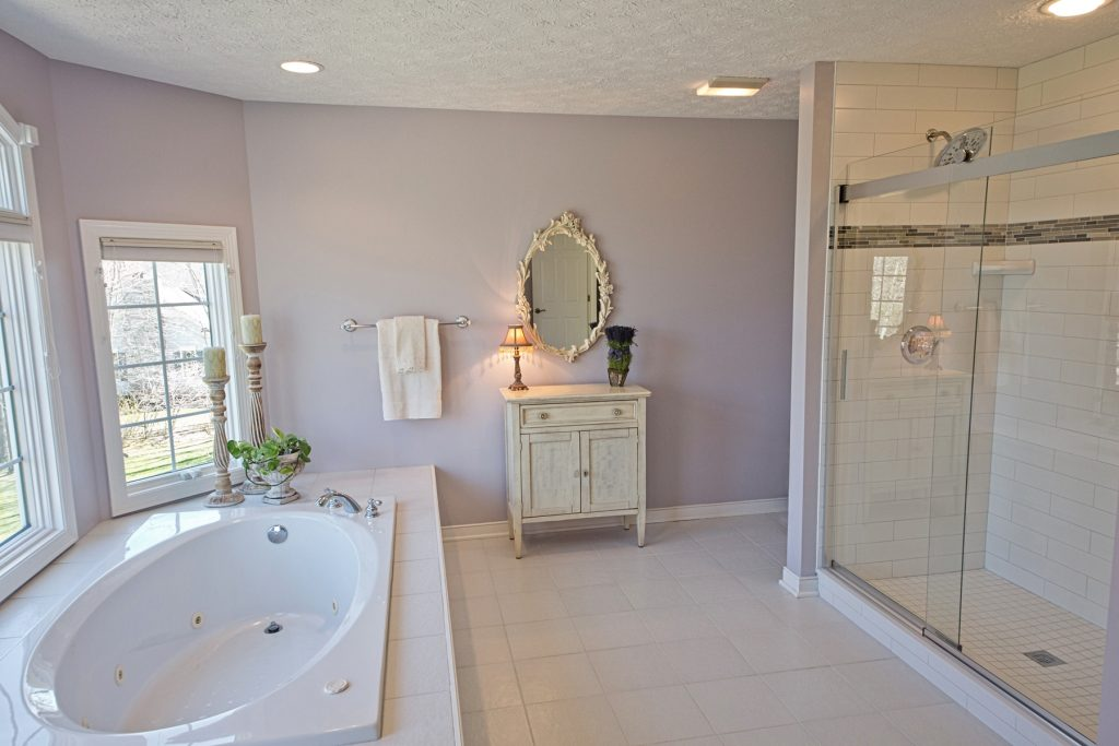 Bathroom with white bathtub and glass shower