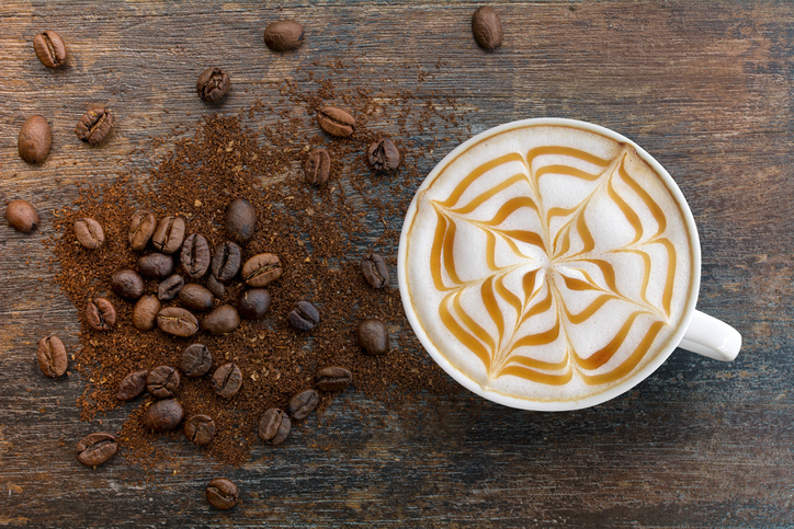 Hot Cappuccino coffee with zigzag caramel motif or spiderweb art floating on top and coffee beans with ground on wooden background. Coffee break at retro style coffee shop,t op view.