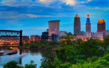 Downtown Cleveland beginning to light up at dusk wtih the Cuyahoga River winding past