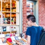 young asian man student boy checking out used books