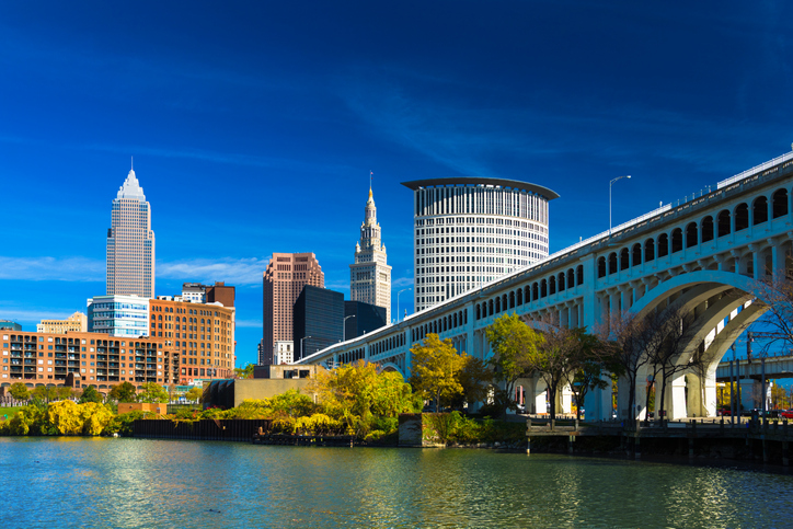 Downtown Cleveland skyline (featuring Key Tower) with the Cuyahoga River, Detroit-Superior Bridge, Autumn colored trees, and a deep blue sky with wispy clouds.  Wide Angle.