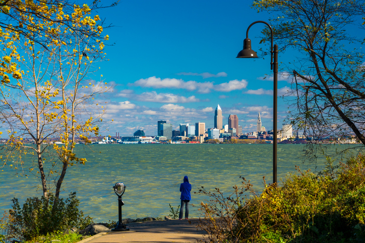 "A woman wearing a hood looks at the Cleveland Skyline from a park just beside Lake Erie""n"